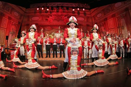 Ein Foto der Tanzgruppe auf der Bühne, im Hintergrund sieht man den stehenden und klatschenden Elferrat, davor stehen Erhengardisten und im Vordergrund stehen die Tanzgruppe und davor die Marieschen im spagat