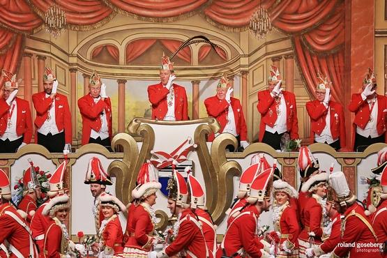 Foto des Elferrats während der großen Bürgersitzung, im Vordergrund tanzt die Tanzgruppe
