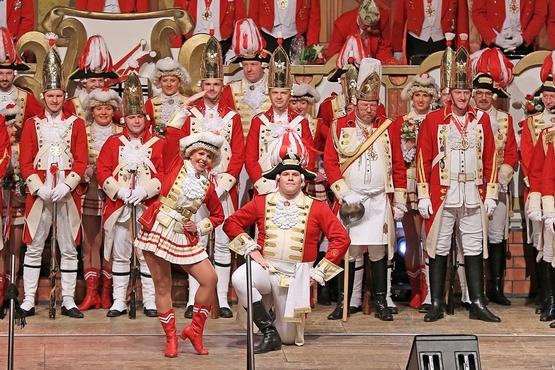 Foto der Ehrengardisten auf der Bühne der großen Bürgersitzung, im Hintergrund stehen die Gardisten und im Vordergrund post das Tanzpaar