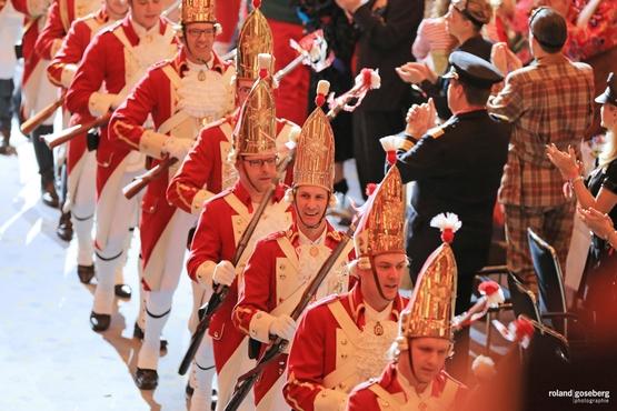 Auf diesem Foto sieht man die Ehrengardisten beim Einzug durch den Saal während Stehende Menschen klatschen