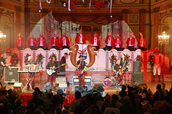 auf diesem Foto sieht man Brings auf der Bühne der großen Bürgersitzung, im hintergrud steht der Elferrat auf dem Podest