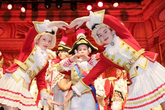 Verkleidete Kinder zeigen Herzen mit Händen