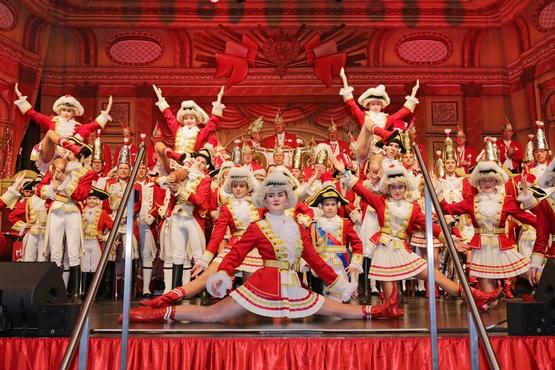 Das Cadettencorps auf der Bühne, im Hintergrund werden Marieschen in einer Hebefigur gehalten und um Vordergrund macht ein Marieschen einen Spagat