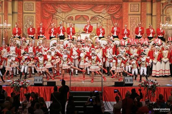 Foto der Bühne der großen Bürgeritzung, im Hintergrund steht der Elferrat auf dem Podest und klatscht während im Vordergrund die Tanzgrupppe alles gibt