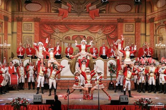 Ein Foto der Tanzgruppe auf der Bühne, im Hintergrund sieht man den stehenden und klatschenden Elferrat, davor stehen Erhengardisten und im Vordergrund stehen die Tänzer der Tanzgruppe mit Hebefiguren