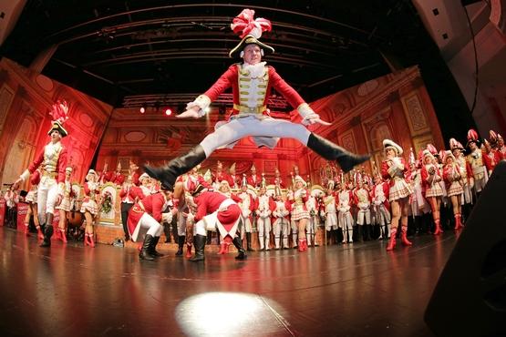 Foto eines Tänzers auf der Bühne, welcher einen beeindruckenden Sprung ausführt, im Hintergrund stehen Klatschende Ehrengardisten
