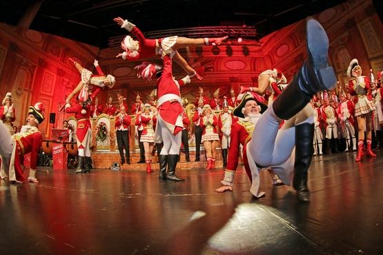 Die Tanzgruppe auf der Bühne beim Tanzen, im Hintergrund stehen die Ehrengardisten und Klatschen, davor werden Marieschen in die Luft geworfen und im Vordergrund tanzen zwei Gardisten
