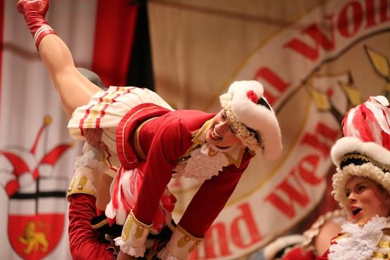 Auf diesem Foto sieht man wie ein Tanzmariechen in einer Hebefigur in der Luft gehalten wird