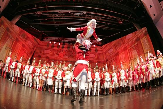 Foto des Tanzpaares der Ehrengarde auf der Bühne wie sie eine Hebefigur machen, im Hintergrund stehen Ehrengardsiten