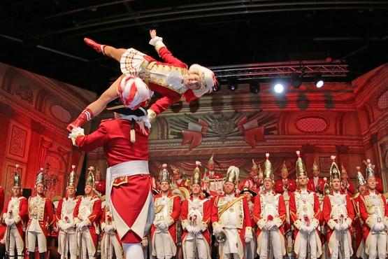 Foto von einer Hebefigur des Tanzpaares auf der Bühne, im Hintergrund stehen die Ehrengardisten und schauen gespannt zu