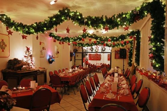 Kleinere Tische, sowie eine Lange Tafel und vielzählige Stühle. Es hängt Weihnachts-Deko