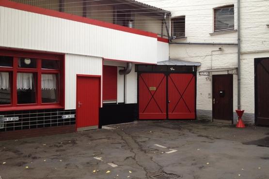 Der Hof des Zeughauses mit Blick auf das rot lackierte Holztor. Auch die restlichen Türen sowie die Fensterrahmen sind rot.