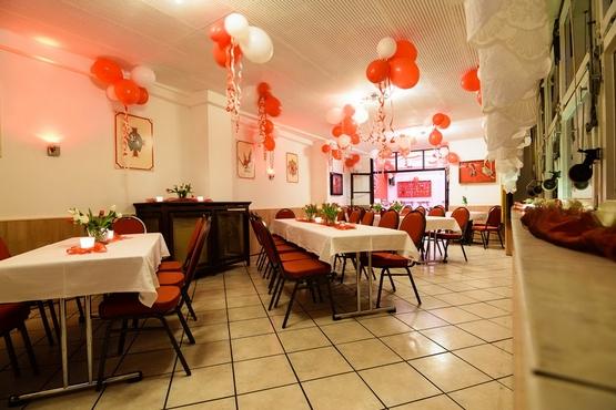 Die Tische sind mit weißen Tischdecken geschmückt. An der Decke schweben rot-weiße Ballons.