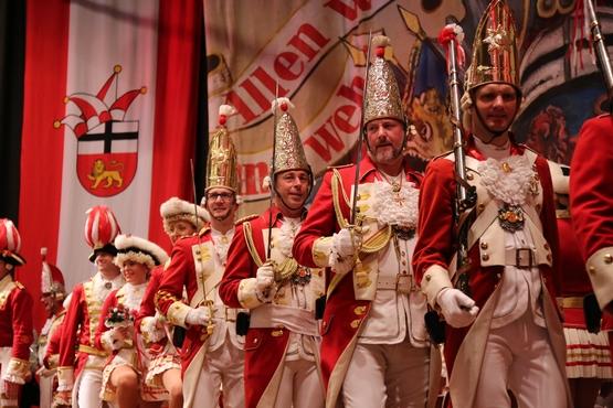 Die Ehrengardisten stehen in uniform auf der Bühne und halten ihre Säbel nach oben