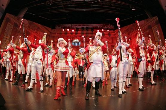 Foto von Ehrengardisten auf der Bühne, die Gardisten halten ihre Gewehre vor sich in die Höhe