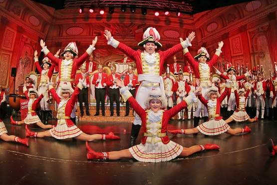 Foto der Tanzgruppe auf der Bühne, im Hintergrund steht der Elferrat und im Vordergrund machen die Marieschen einen Spagat