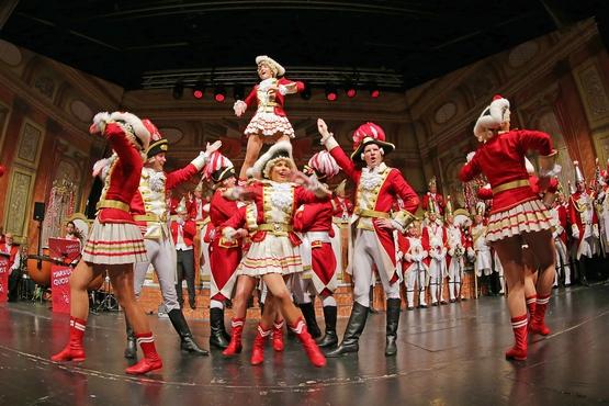 Ein Foto der Tanzgruppe in Aktion auf der Bühne, tanzende Gardisten im Vordergrund und im Hintergrund stehen Gardisten und feiern