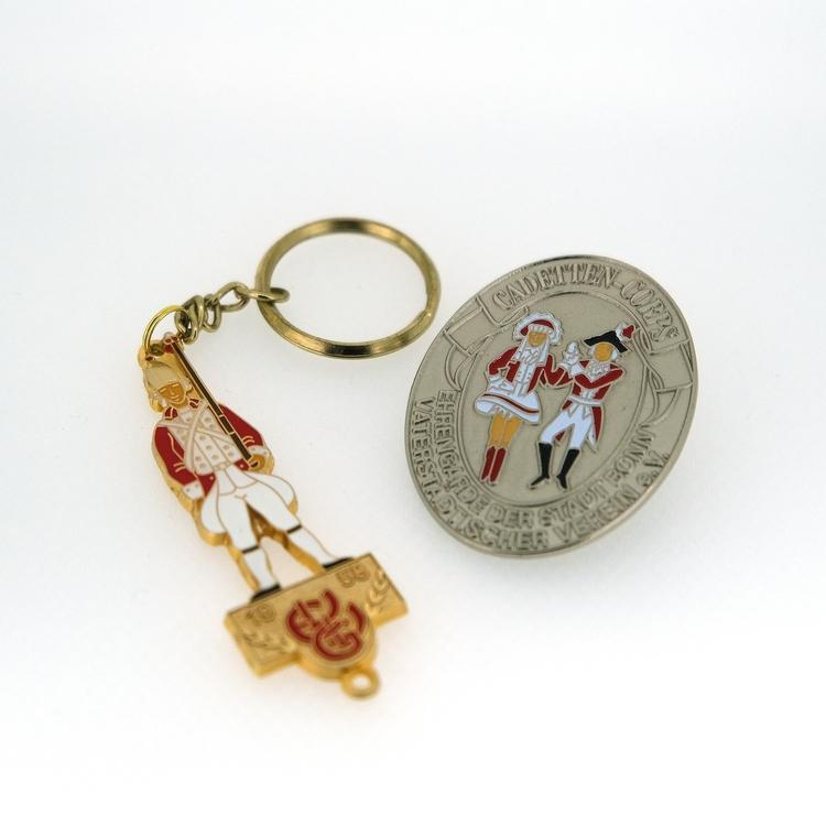 Ein goldener Schlüsselanhänger der Ehrengarde und ein Silberner Pin des Cadettencorps