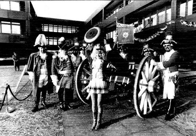 Schwarzweiß Fotografie von Ehrengardisten und Ehrengardistinnen vor einer altmodischen Kanone.