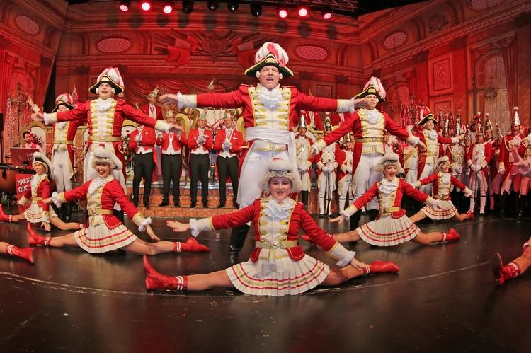 Tänzerinnen führen einen Spagat auf, die Tänzer Hintergrund stehen in einer T-Pose.