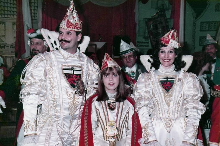 Prinz und Bonna posieren 1983 gemeinsam mit der Kinderbonna für ein Foto. Sie sind in feierliche weiß-goldene Kleidung gehüllt.