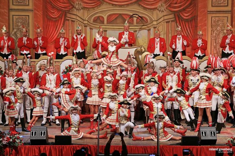 Foto der Tanzgruppe bei einem Auftritt. In der ersten Reihe führen die Tänzerinnen einen Spagat auf im Hintergrund wird eine Tänzerin in die Luft gehoben.