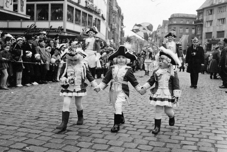 Altes Foto von Kindern welche händchenhaltend am Straßenkarneval teilnehmen.