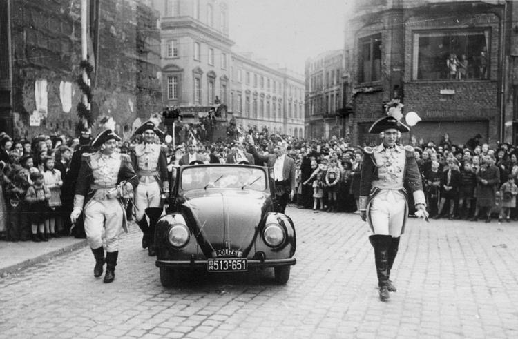 Uniformierte Ehrengardisten Marschieren begleitet von einem VW-Käfer der Polizei durch die Bonner Innenstadt. Die schwarzweißaufnahme ist aus den 50er Jahren.