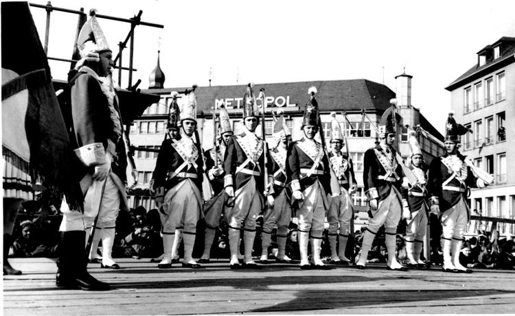Die Ehrengardisten versammeln sich auf dem Bonner Marktplatz. Im Hintergrund ist der Schriftzug des Metropol Kinos zu erkennen.