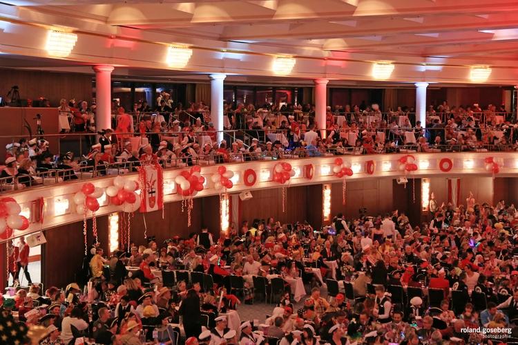 Foto des rot-weiß geschmückten und mit unzähligen Menschen gefüllten Saales der großen Bürgersitzung
