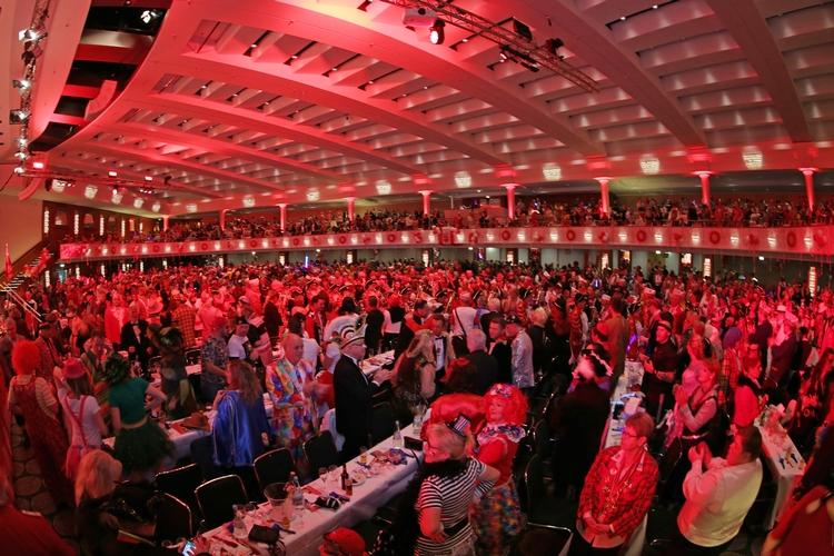 Im großen in rot - weißen Farben gehüllten Saal sitzen unzählige kostümierte Gäste an den Tischen.