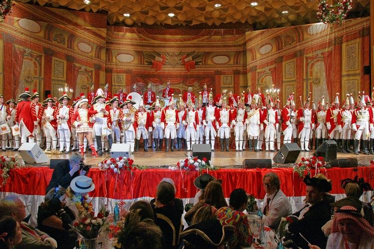 Die gesamte Tanzgruppe steht auf einer rot-weiß geschmückten Bühne und wartet auf Ihren Auftritt.
