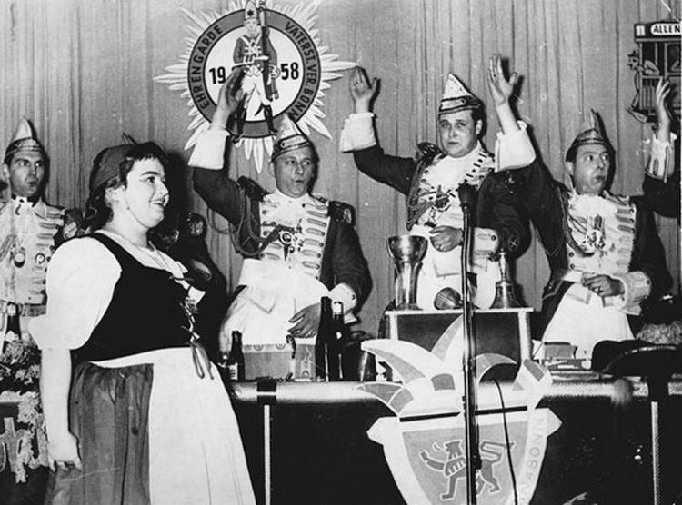 Schwarz-weiß Fotografie vom Infanterie-Treffen, Ehrengardisten feiern und heben ihre Hände in die Luft. Im vordergrund ist eine lachende Dame zu erkennen.
