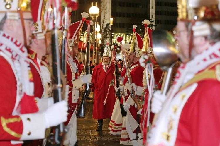 Bewaffnete Ehrengardisten stehen links und rechts in Reihe und bilden so einen Durchgang, an dessen Ende der Kommandant steht.