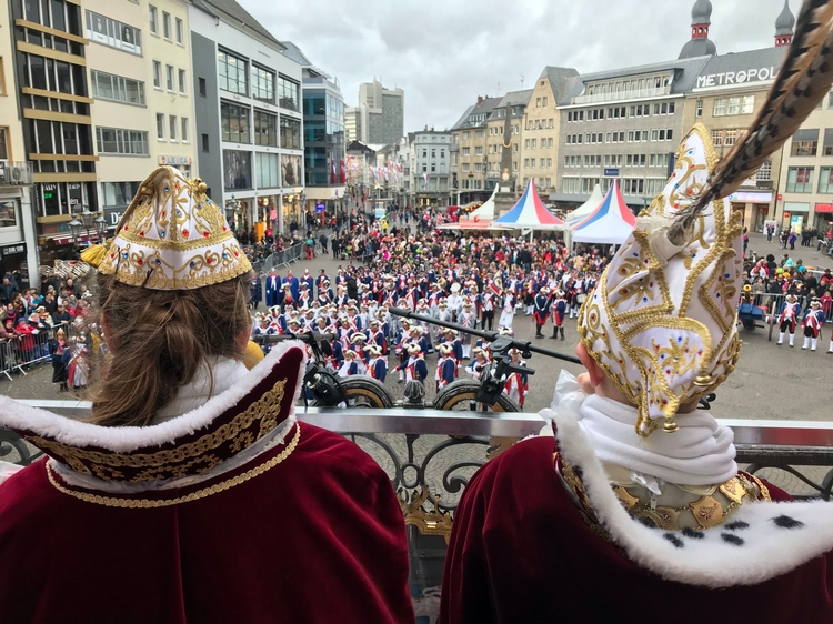 Das Kinderprinzenpaar auf den Stufen des Bonner Rathauses. Auf dem Marktplatz sind die Bonner Stadtsoldaten versammelt.