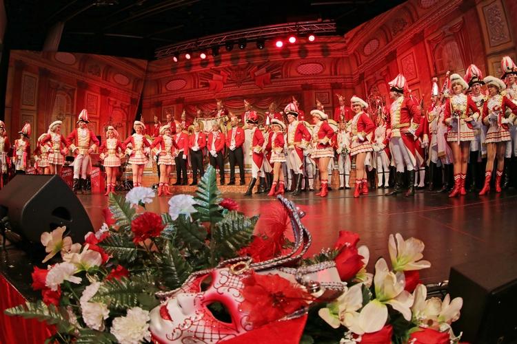 Mitglieder der Ehrengarde posieren auf der Bühne. Im Vordergrund sind Blumensträuße sowie eine rot-weiße Maske zu sehen.
