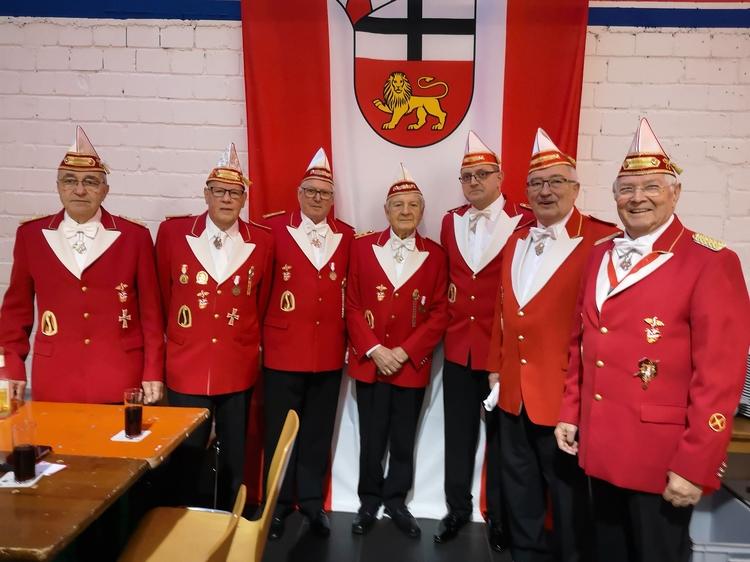 Die Mitglieder des Mööden Senat posieren in Litewka gekleidet vor einem Banner mit dem Formationslogo.