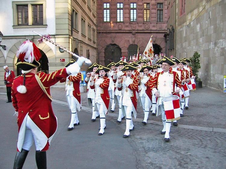 Ein Musikzug der Ehrengarde zieht durch die Straßen. Allen vorran der Dirigent mit seinem Stab.