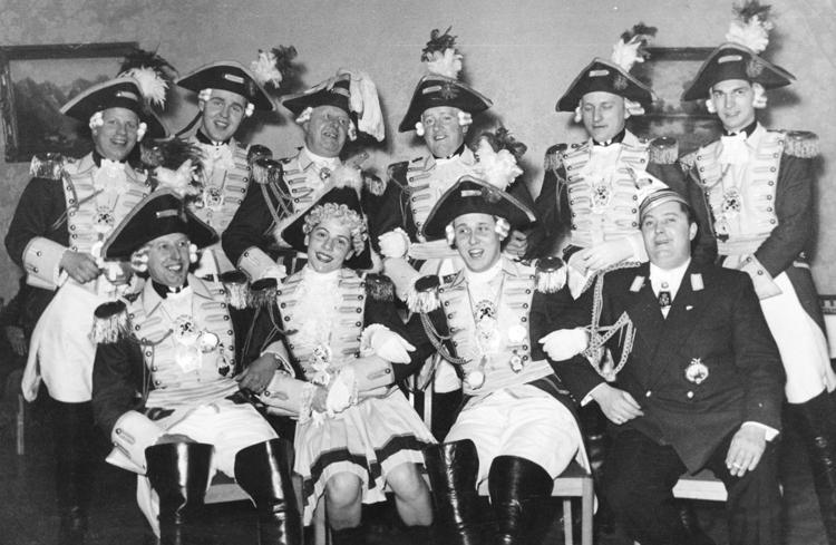 Ein altes schwarzweiß Foto zeigt kostümierte EhrenGardisten, welche fröhlich auf Stühlen hin und her wippen.