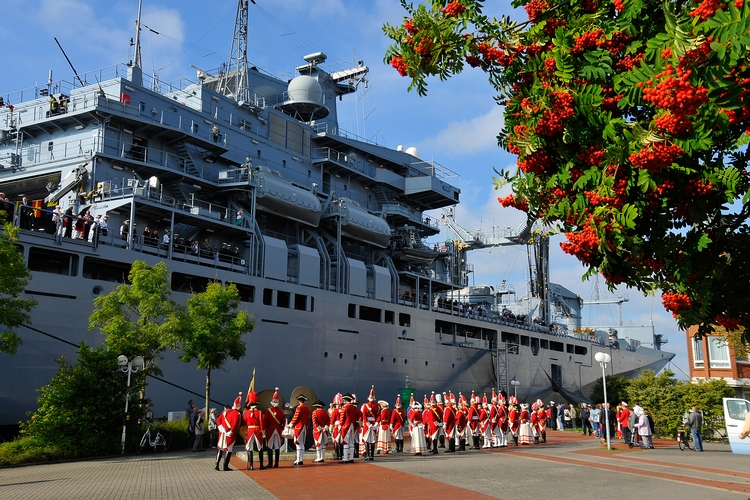 Die Ehrengardisten stehen staunend vor dem gewaltigen Einsatzgruppenversorgerschiff.