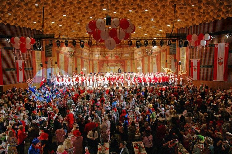 Foto der Tanzgruppe beim Auftritt in einem großen mit unzählig vielen, kostümierten Menschen gefüllten Saal.