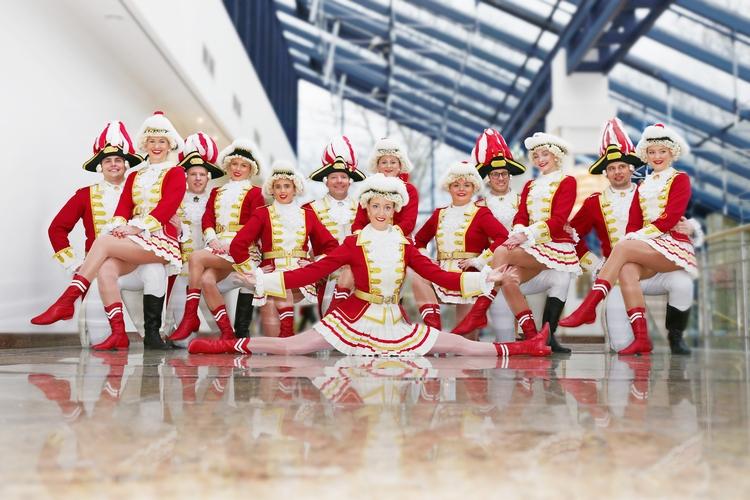 Ein Gruppenbild der Tanzgruppe. Im Vordergrund ist eine Tänzerin im Spagat im Hintergrund ist ein schräges Glasdach zu erkennen.