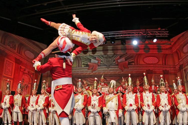 Die Tänzerin wird in die Luft gehoben und führt dort eine Figur auf. Im Hintergrund schauen uniformierte Mitglieder dem Spekatel zu.