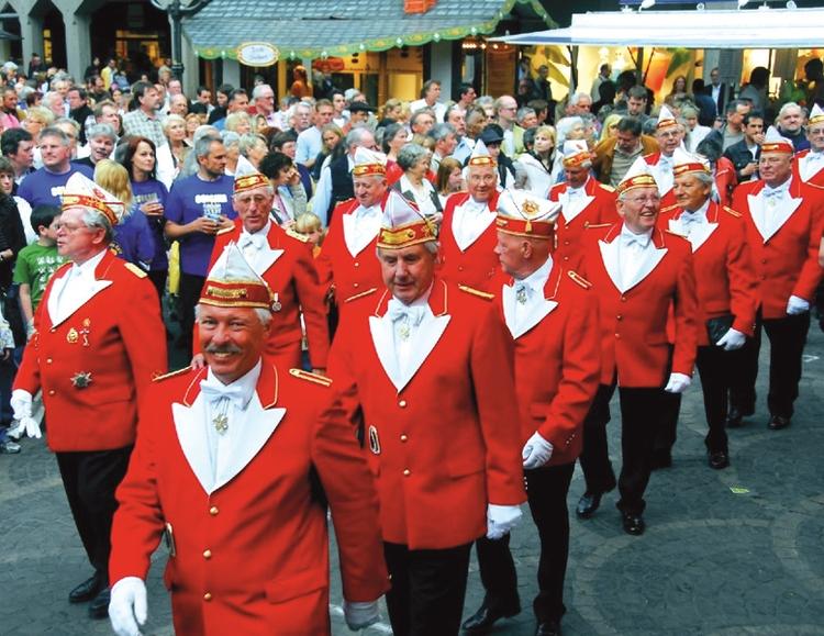 In rot-weiße Litewka gekleidete Mitglieder der EhrenGarde ziehen über den einen Jahrmarkt auf dem Münsteplatz.