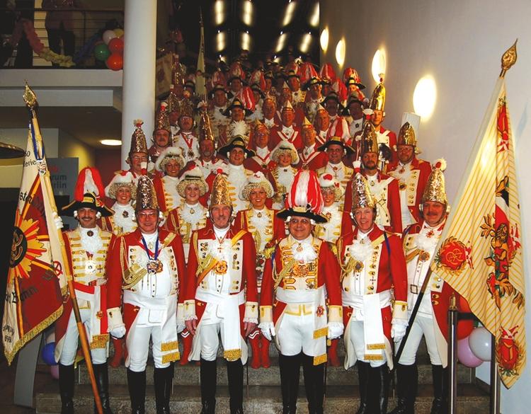 Die stolzen Mitglieder der damaligen Artillerie posieren uniformiert auf einer großen Treppe. Im Vordergrund stehen zwei mit Wappen verzierte Fahnen.