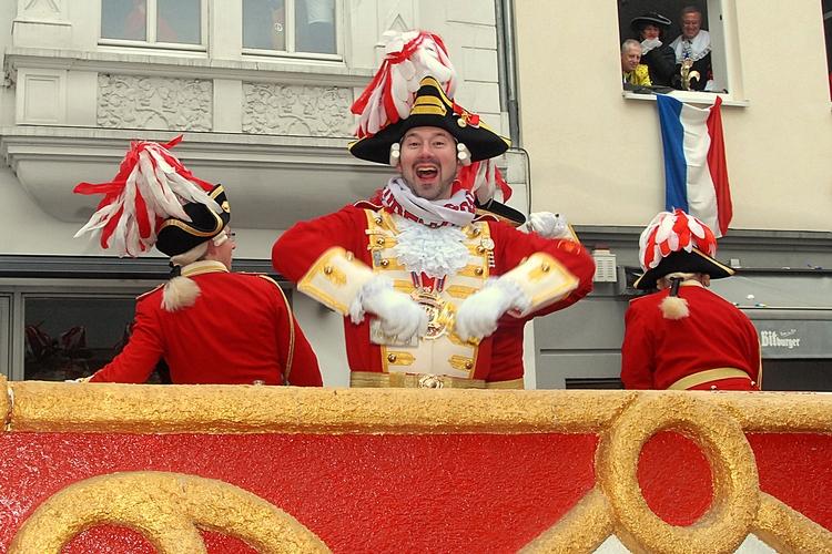 Ein Ehrengardist hat sichtlich Spaß während der Bonner Karnevalszug durch die Friedrichstraße zieht.