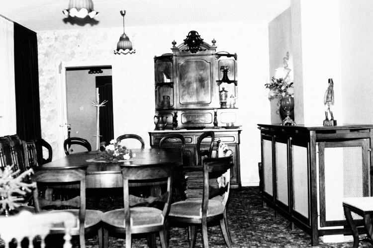 Das Interieur des alten Zeughaus. Zusehen sind ein antiker Schrank sowie ein simpler, runder Holztisch mit einigen Stühlen.