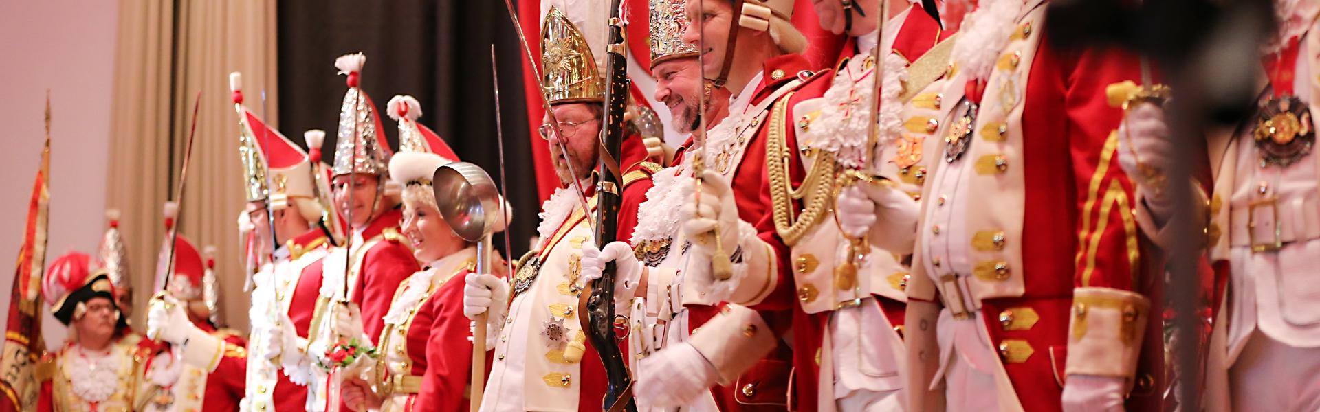 Vertreter aller Formationen stehen auf der Bühne, sie halten Waffen wie Degen, Bajonett oder Suppenkelle in den Händen.