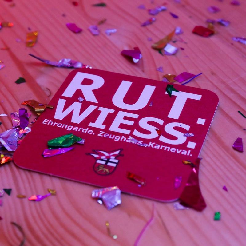 Auf dem Holztisch liegt ein Bierdeckel der Ehrengarde mit der Aufschrift: Ruut Wies. Buntes Konfetti liegt umher.
