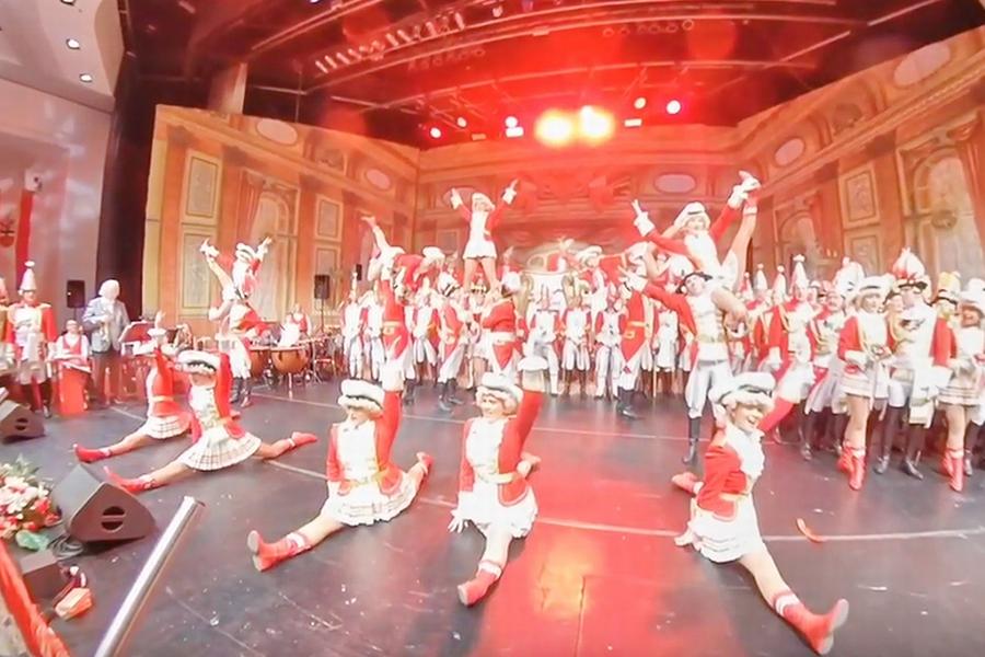 Screenshot aus dem video der Tanzgruppe der EhrenGarden der Stadt Bonn: Im Vordergrund der Bühne führen die Tänzerinnen einen Spagat auf, im Hintergrund heben die Tänzer ihre Tanzpartnerinnen in die Luft